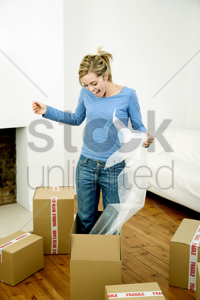 woman standing in a box holding bubble pack stock photo