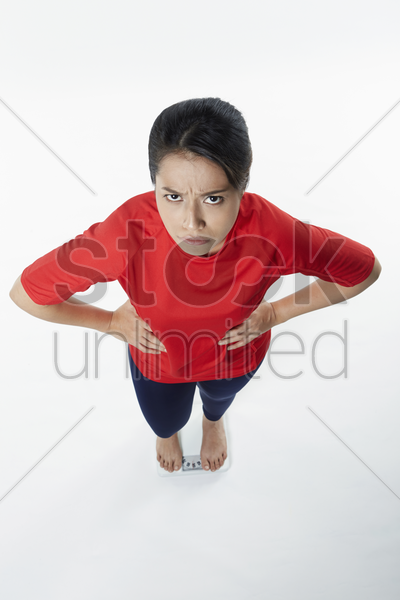 woman standing on the weighing machine stock photo