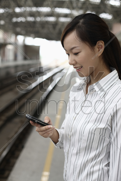 woman standing on train station platform text messaging on the phone stock photo