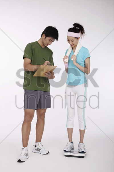 woman standing on weight scale, man writing on clipboard stock photo