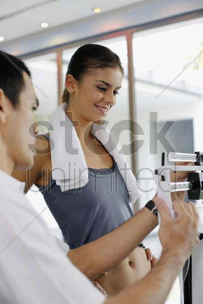woman standing on weight scale, personal trainer checking her weight stock photo
