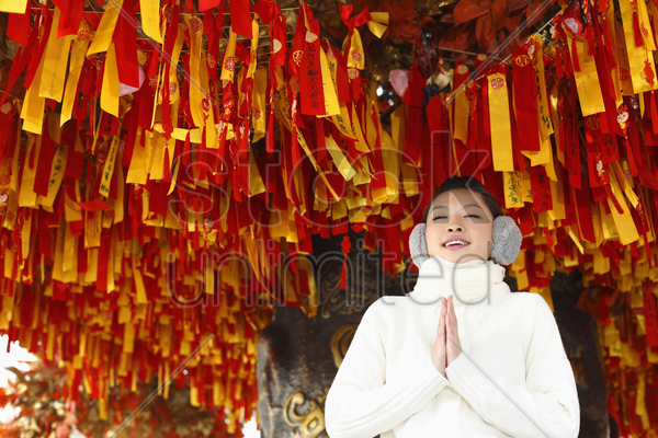 woman standing under a wishing tree with her hands clasped and her eyes closed stock photo