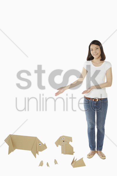 woman standing with paper animals by her side stock photo