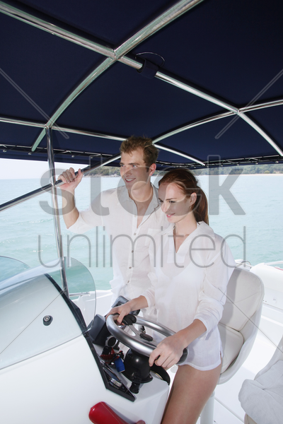 woman steering speedboat, man standing beside her stock photo