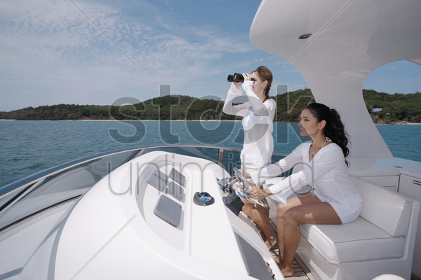 woman steering yacht while another woman is looking through binoculars stock photo