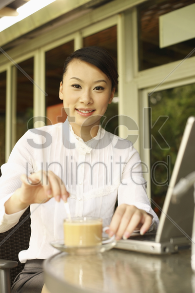 woman stirring her cup of coffee, smiling stock photo