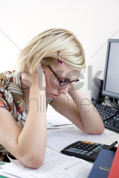 woman stressed working at desk in a home office stock photo