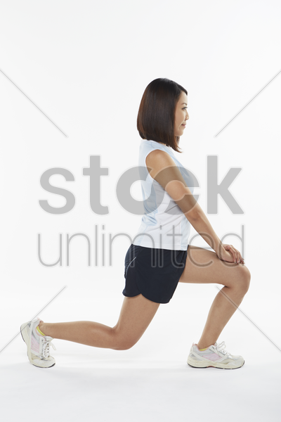 woman stretching and doing lunges, facing left stock photo