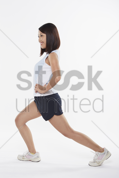 woman stretching and doing lunges, facing right stock photo