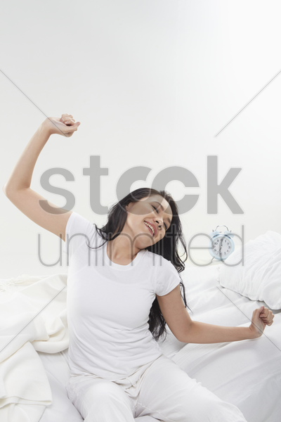 woman stretching on her bed stock photo