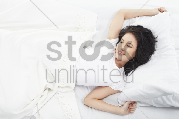 woman stretching on the bed stock photo