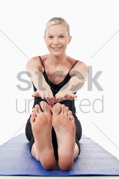 woman stretching on yoga mat stock photo