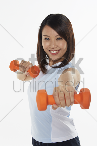 woman stretching using dumbbells stock photo