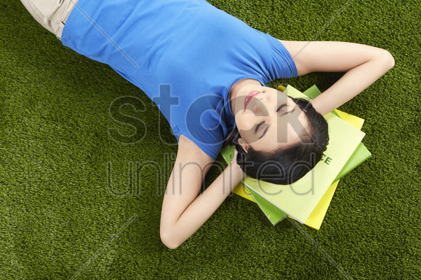 woman studying while laying on the grass stock photo