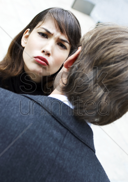 woman sulking in front of a man stock photo