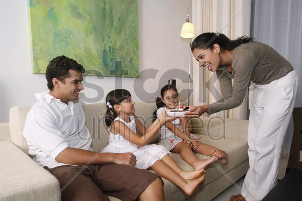 woman surprising girl with chocolate cake, family sitting in the living room stock photo