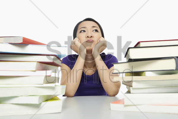 woman surrounded by books, looking bored stock photo