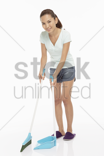 woman sweeping the floor with a broom and dustpan stock photo