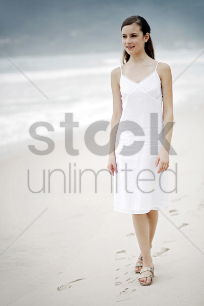 woman taking a stroll along the beach stock photo