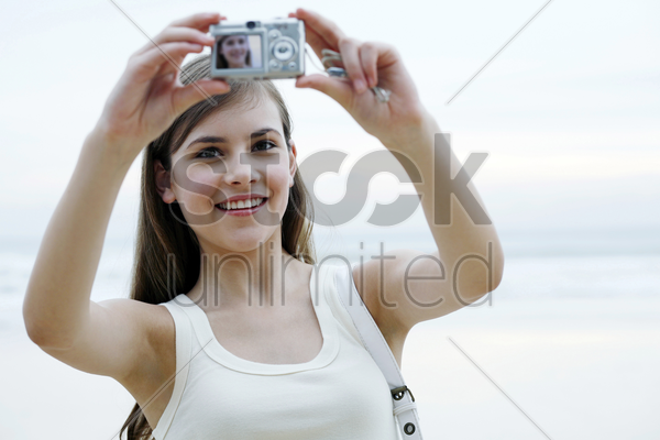 woman taking her own picture with a digital camera stock photo