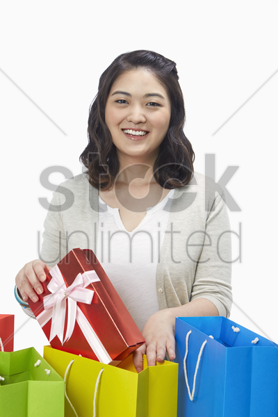 woman taking out a gift box from the paper bag stock photo