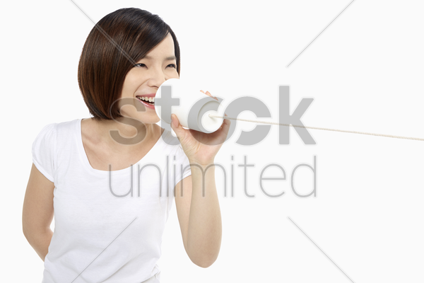 woman talking into a paper cup phone stock photo
