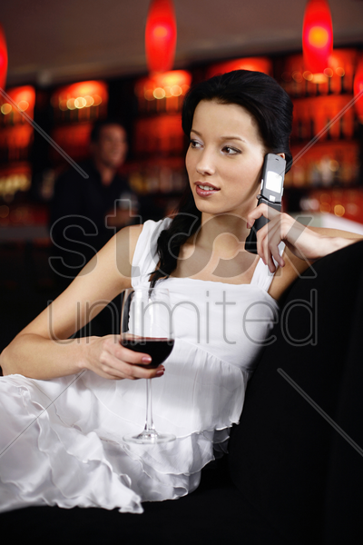 woman talking on the mobile phone while holding a glass of wine stock photo