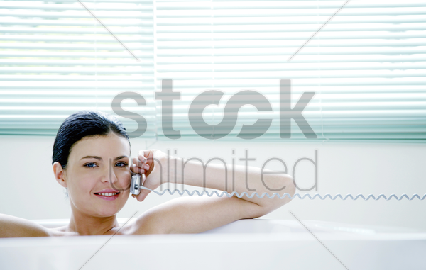 woman talking on the mobile phone while sitting in the bathtub stock photo