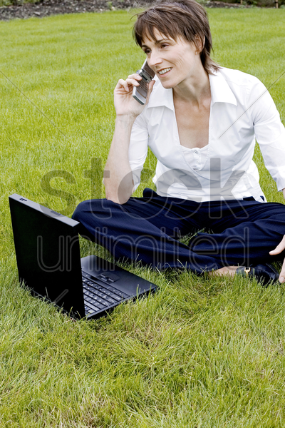woman talking on the mobile phone while using laptop stock photo
