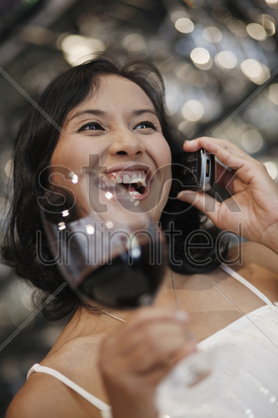 woman talking on the phone and holding a glass of red wine stock photo