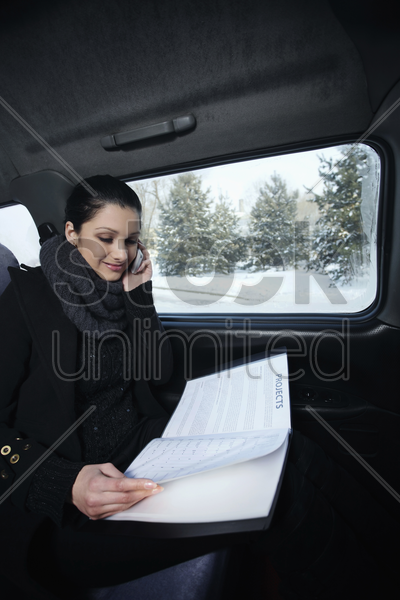 woman talking on the phone and reading document while traveling in the car stock photo