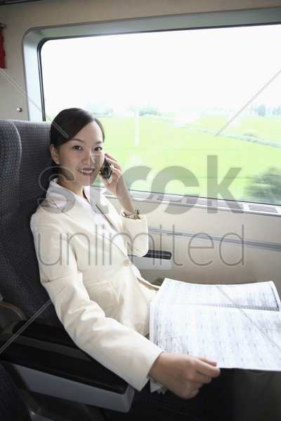 woman talking on the phone and reading newspaper while traveling on the train stock photo
