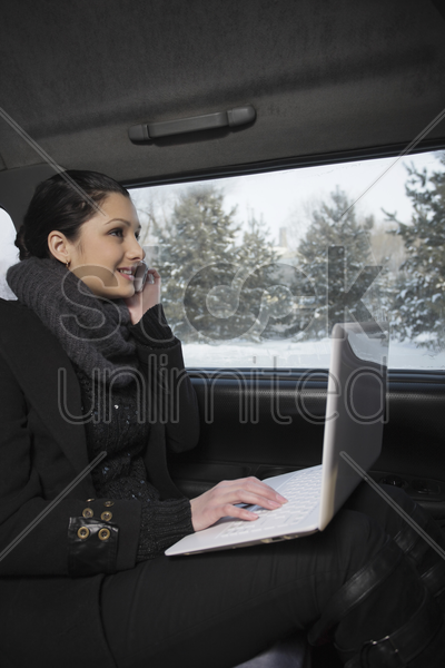 woman talking on the phone and using laptop while traveling in the car stock photo