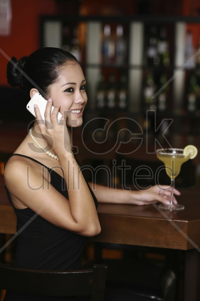 woman talking on the phone at the bar stock photo