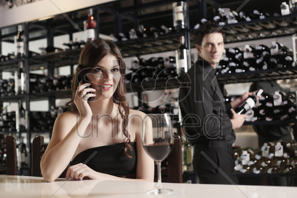 woman talking on the phone, man selecting wine bottle in the background stock photo