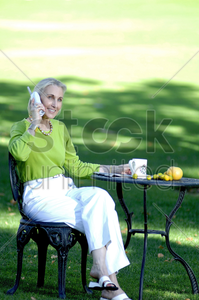 woman talking on the phone while enjoying a cup of coffee in the garden stock photo