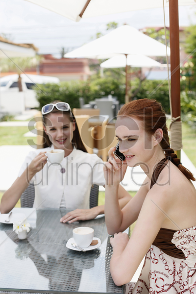 woman talking on the phone while her friend is enjoying coffee stock photo