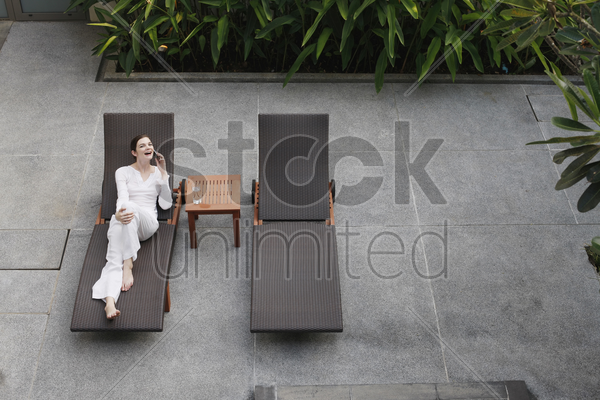 woman talking on the phone while relaxing on lounge chair stock photo