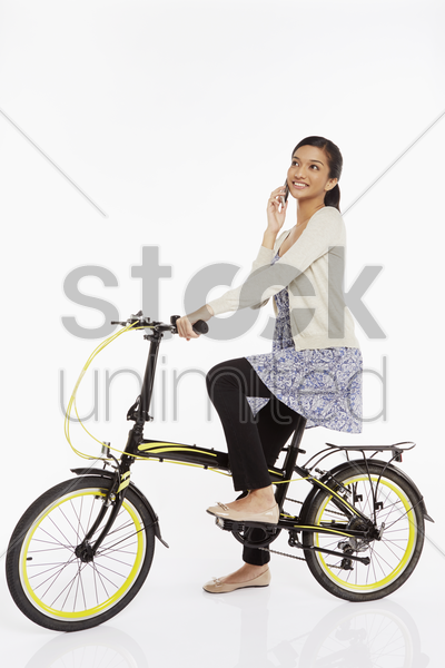 woman talking on the phone while riding a bicycle stock photo