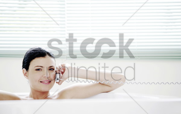 woman talking on the phone while sitting in the bathtub stock photo
