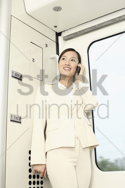 woman talking on the phone while traveling in train stock photo