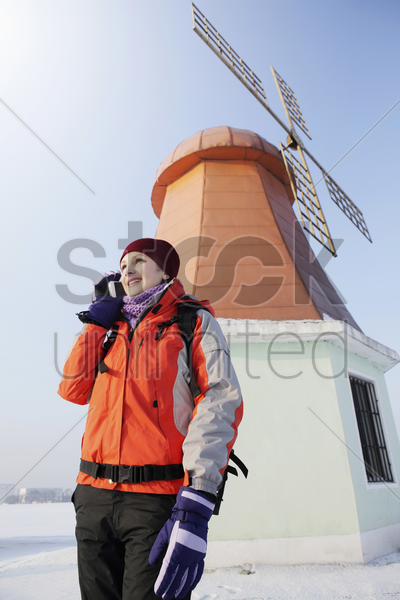 woman talking on the phone, windmill in the background stock photo