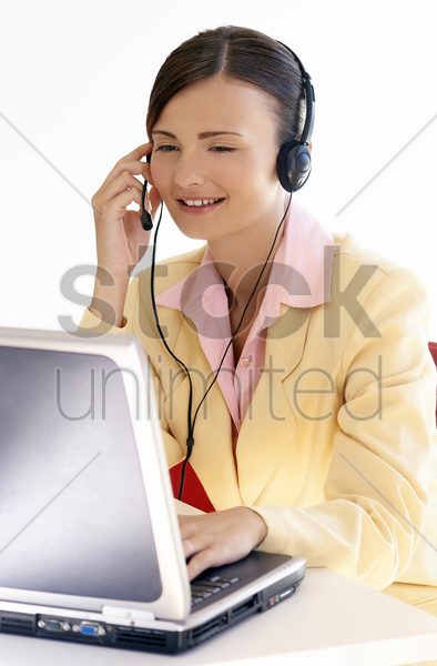 woman talking on the telephone headset while using the laptop stock photo