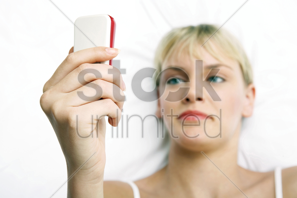 woman text messaging while lying on the bed stock photo