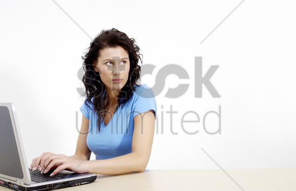 woman thinking while using laptop stock photo
