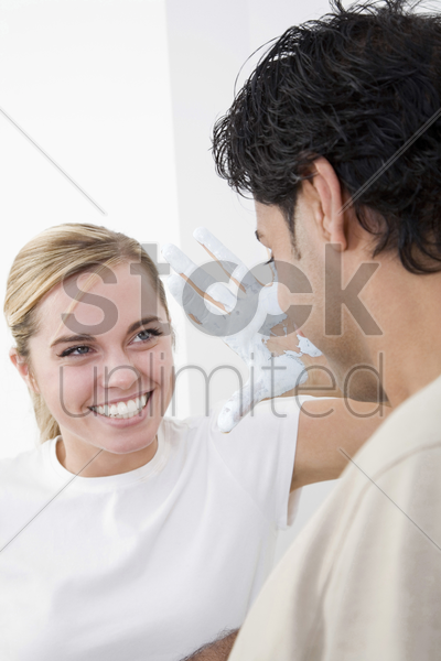 woman threatening boyfriend with her paint covered hand stock photo