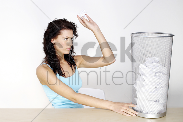 woman throwing crumpled paper into the dustbin stock photo