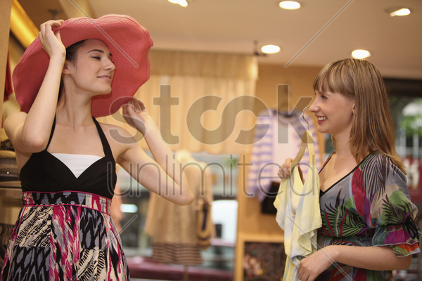 woman trying on a hat while her friend is holding up a blouse stock photo
