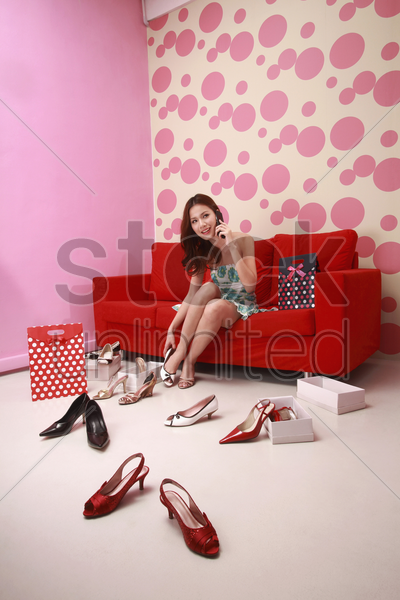 woman trying on different kinds of high heels while talking on the mobile phone stock photo