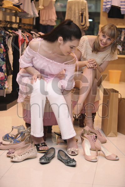 woman trying on shoes while her friend watches from the side stock photo